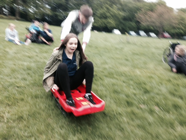 A PALS volunteer taking part in grass sledging